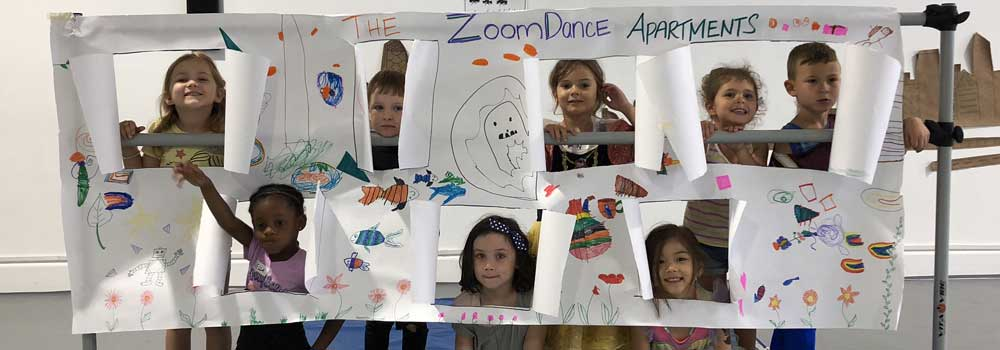 Children looking through cutout windows in a large sheet of decorated paper labeled ZoomDance Apartments.