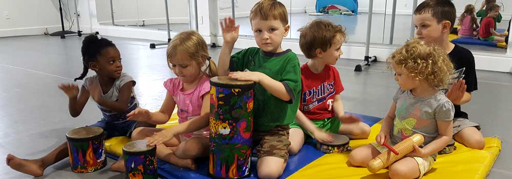 A group of three boys and three girls sitting on the floor playing percussion instruments.