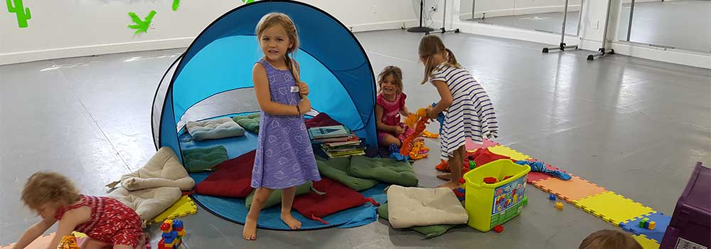 A girl standing in front of a small circular tent filled with cushions as three other girls nearby put together puzzles on the ground.